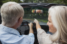 Rear view of smiling mature couple going for a ride together in classy convertible