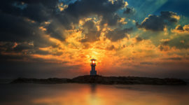 lighthouse with light beam at sunset - triune